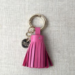 Key holder and bag charms TASSEL in lambskin, fuchsia color and gold - front view on linen background