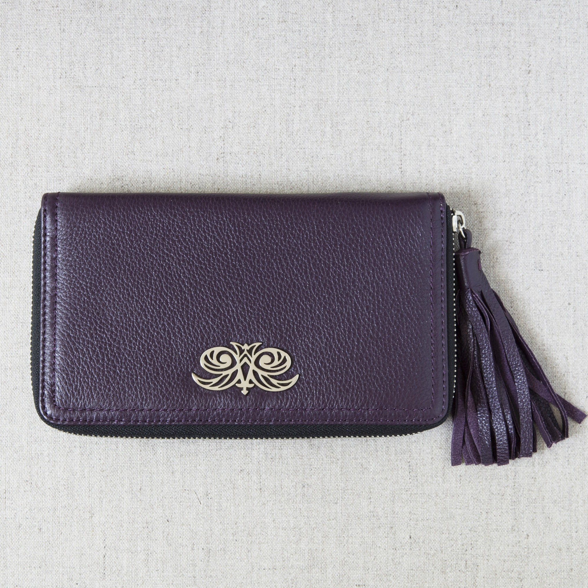 """Zipper organizer """"LISE"""" in grained calfskin purple color and leather tassel - front view on linen"""