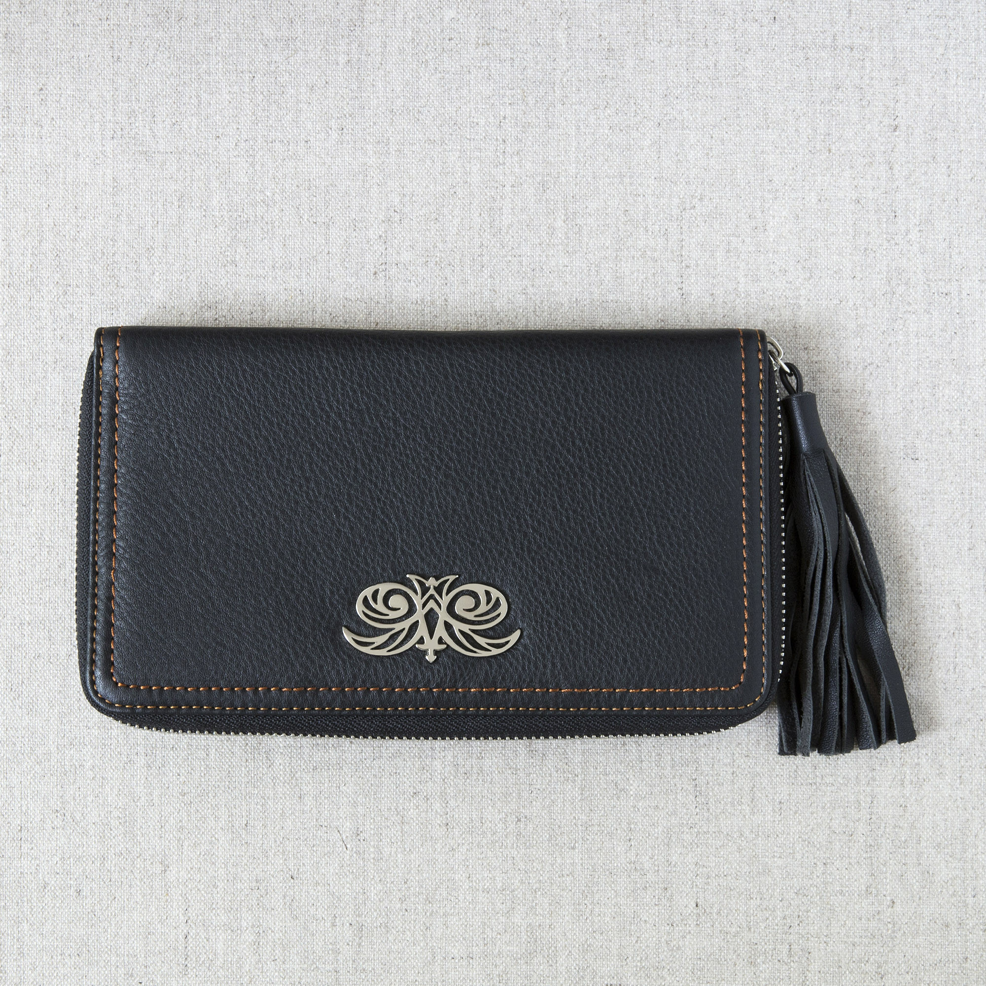 """Zipper organizer """"LISE"""" in grained calfskin black color and leather tassel - front view on linen"""