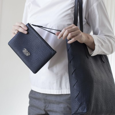 Lambskin zipper pouch with wrist strap, navy blue color - on model