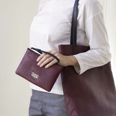 Lambskin zipper pouch with wrist strap, burgundy color - on model